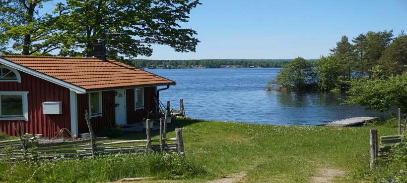 Ein rotes Holzferienhaus direkt am See