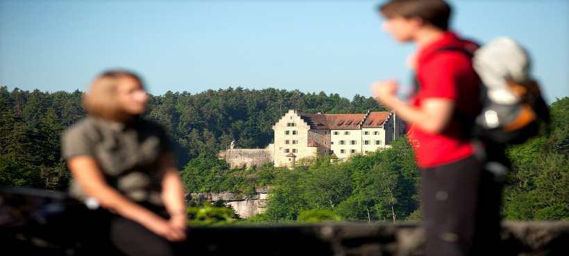 Ein Mann und eine Frau mit einer Burg im Hintergrund