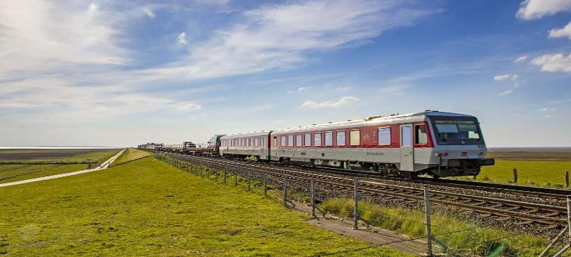 ein Zug unterwegs auf dem Hindenburgerdamm unter blauen Himmel mit nur wenigen Wolken
