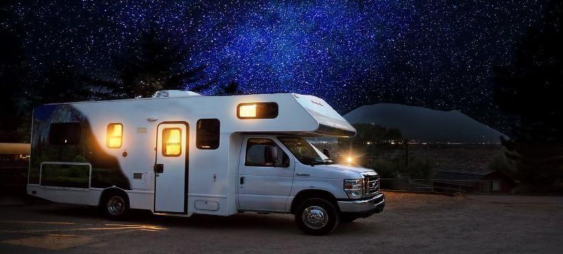 Ein Wohnmobil wo im Hintergrund ein Sternenhimmel zu sehen ist