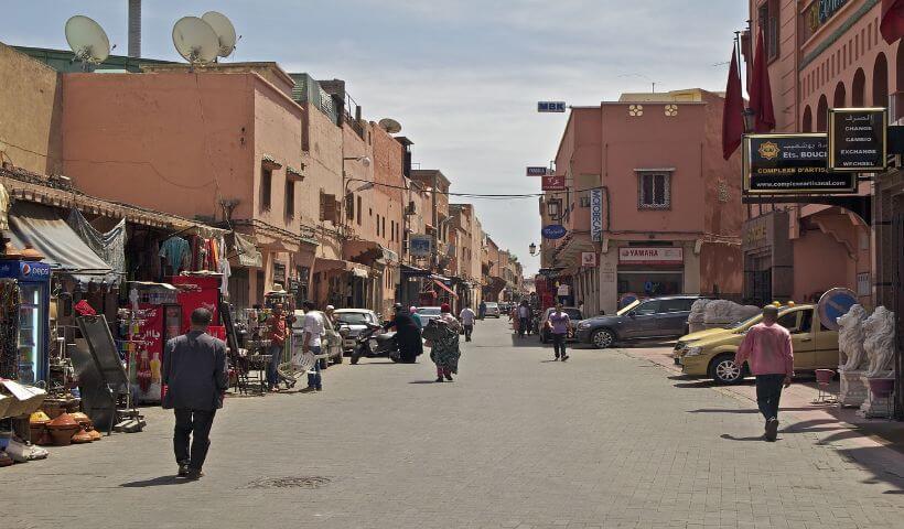 Eine Seitenstraße von Marrakesch mit einigen Läden und Menschen die unterwegs sind