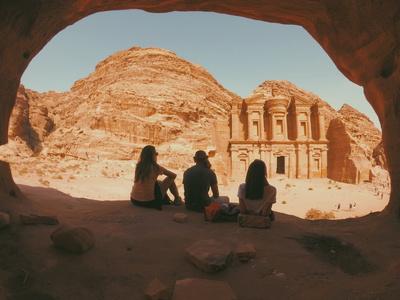 Drei junge Urlauber besichtigen von der Ferne die archäologische Stätte Petra