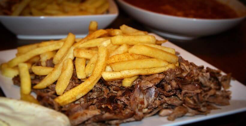 Fleischscheiben ähnlich wie bei einem Kebab mit Pommes oben drauf