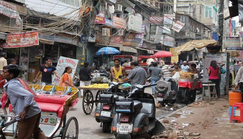 Das Bild zeigt eine chaotische Straße in Delhi mit Straßenverkäufern und vielen Menschen