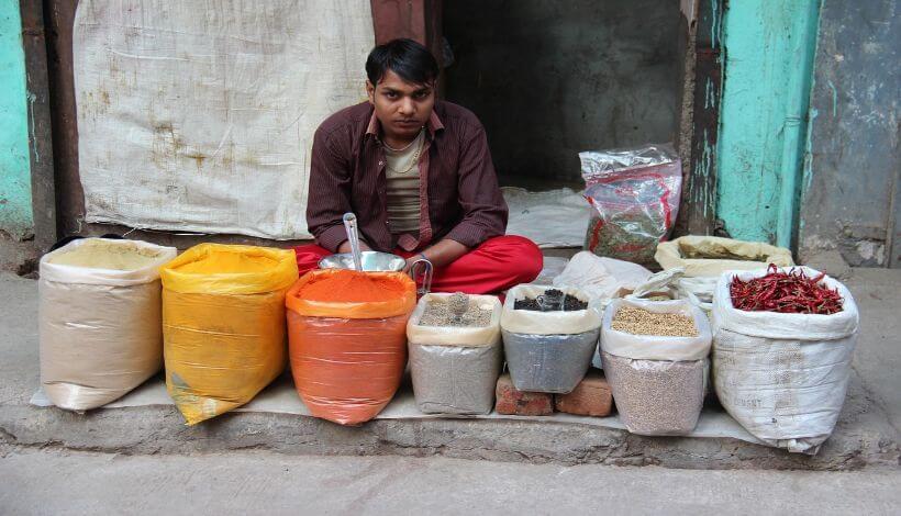 Ein Händler sitzt auf einer Straße von Delhi, mit einigen Säcken von verschiedenen Gewürzen, um Sie zu verkaufen.