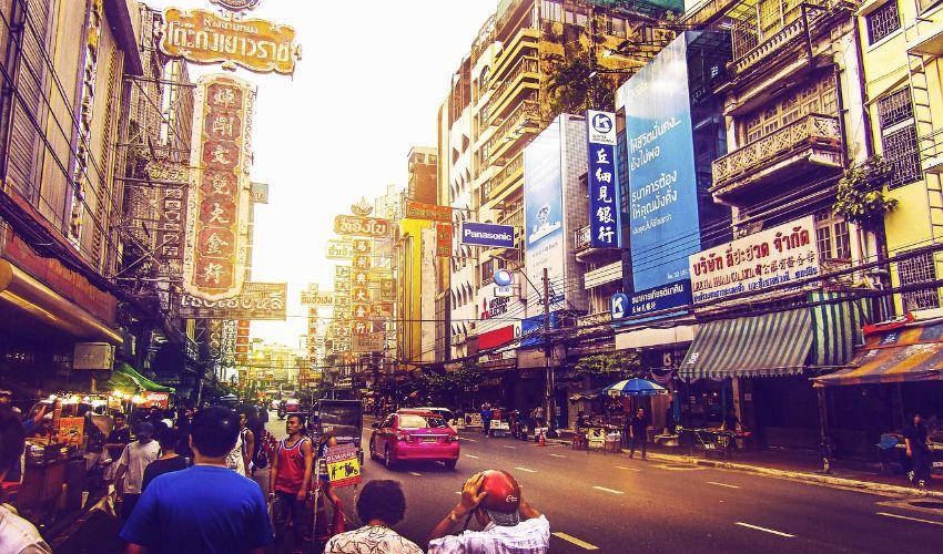 Eine Seitenstraße in Bangkok mit vielen Schildern auf den Häusern und vielen Menschen links und rechts von der Straße.