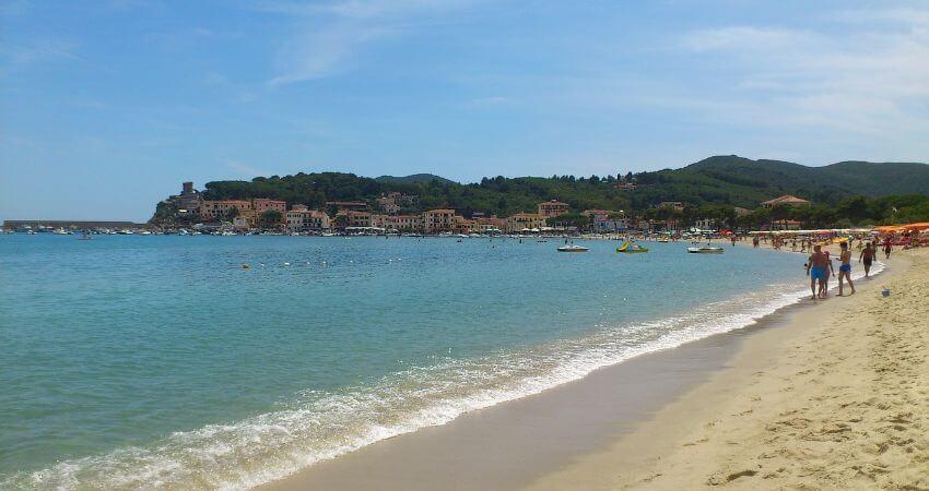 Sandstrand von Elba wo es sich einige Touristen bequem gemacht haben.