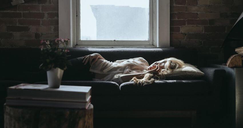 Eine Frau schläft auf einem Sofa.