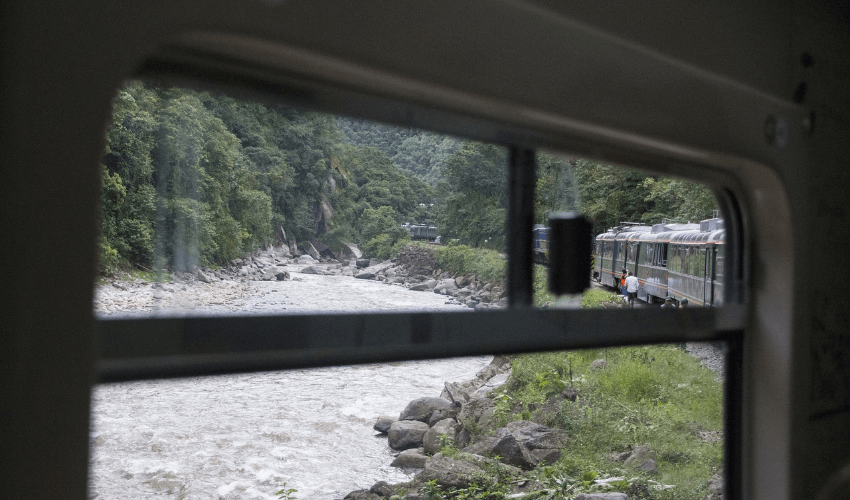 Ein Bild wo noch das Zugfenster rundum zu sehen ist und draußen einen Fluss zeigt und das hintere Ende des Zuges, weil er in eine Kurve einfährt.