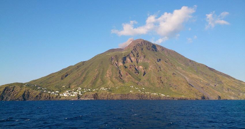 Ein kleines Dorf mit einem Vulkan im Hintergrund.