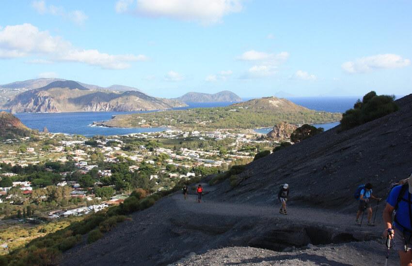 Von einem kargen Vulkan sieht man runter auf eine kleines grün bewachsenes Dorf.