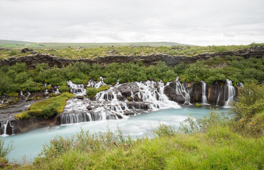 Ein Wasserfall mit grün bewachsenen felsigen Hintergrund.