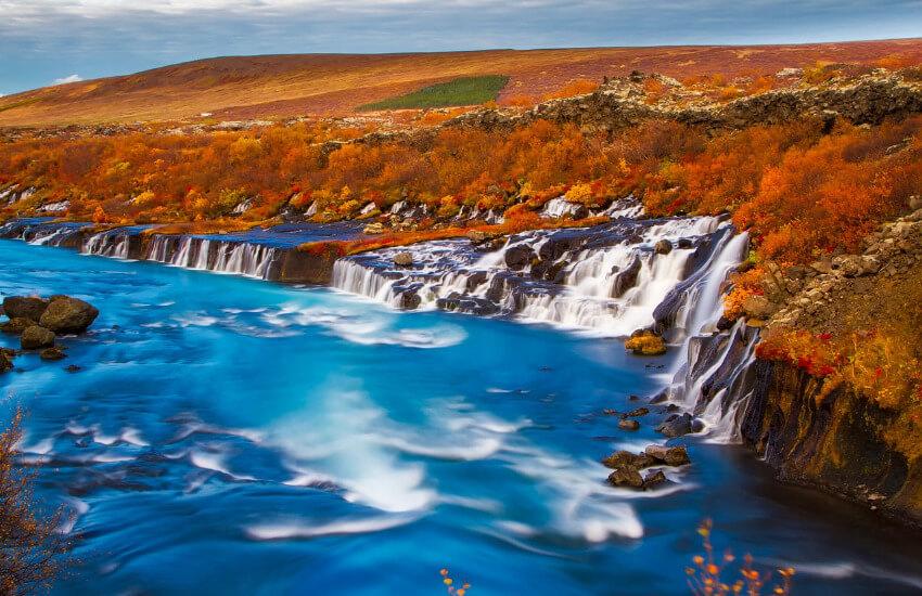 Ein Wasserfall mit vom Herbst gelb und braun gefärbten Pflanzen im Hintergrund.