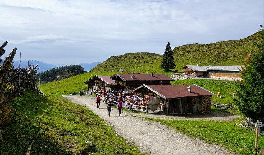 Eine Almhütte in den Bergen von Salzburg, wo sich einige Wanderer erholen.