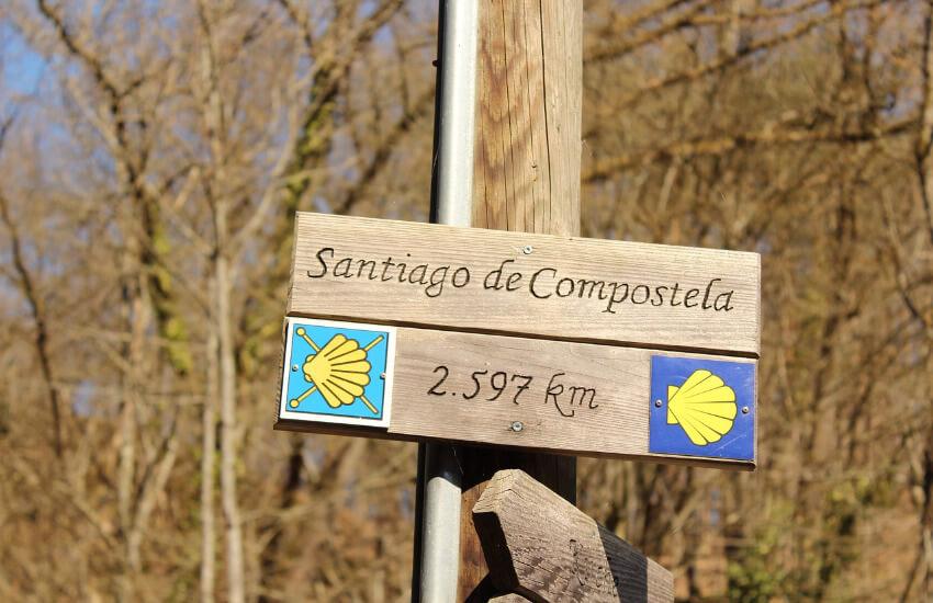 Ein Wegweiser nach Santiago de Compostela, wo die noch zu bewältigen 2597 Kilometer angegeben sind.