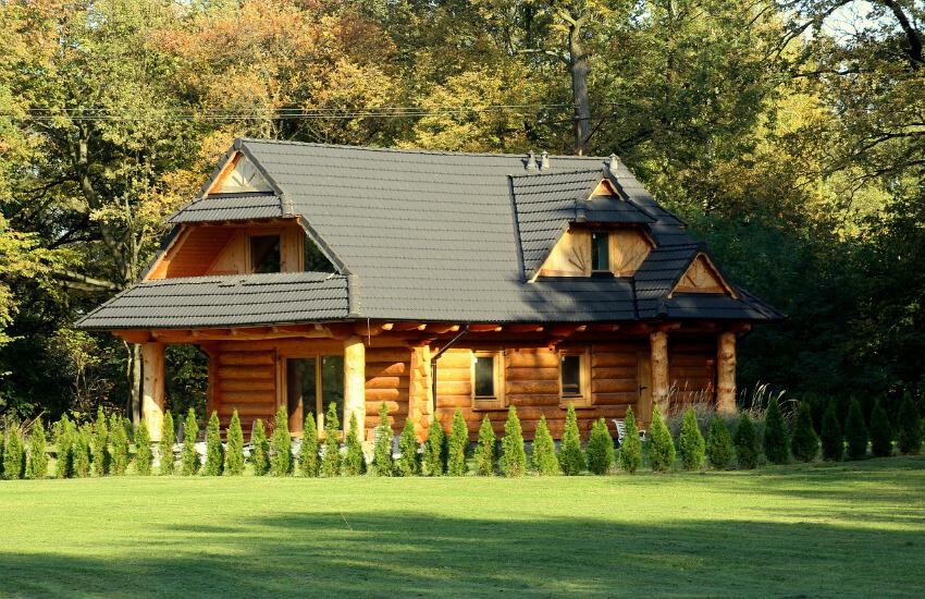 Ein relativ neues Blockferienhaus mit einem frisch gemähten Rasen davor.