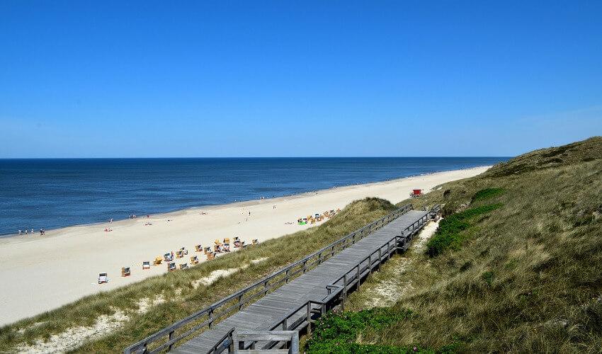 Ein langer Sandstrand entlang der Küste mit einem Holzsteg als Zugang.