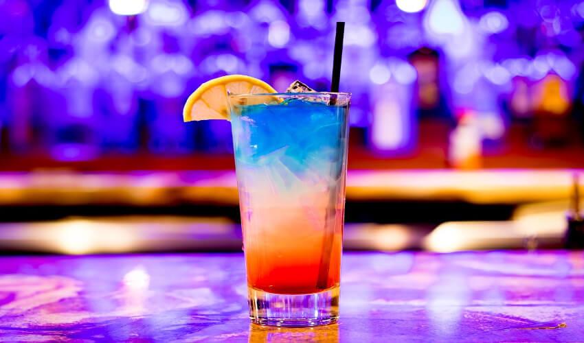 Ein Cocktail mit drei unterschiedlichen Farben, von unten beginnend mit Rot, Transparent, Blau.