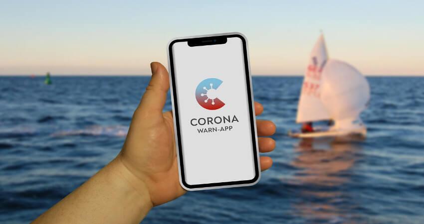 Ein Smartphone in der Hand mit der Corona-Warn-App und davor das Meer