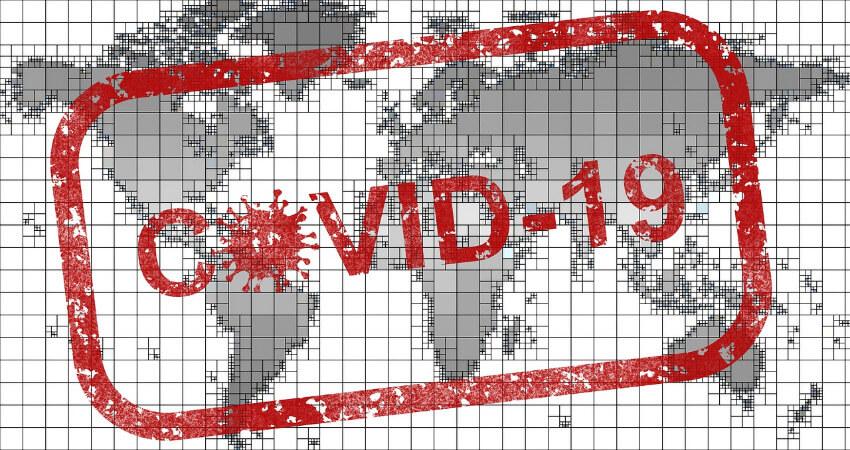 Eine Weltkarte mit Covid 19 eingestempelt