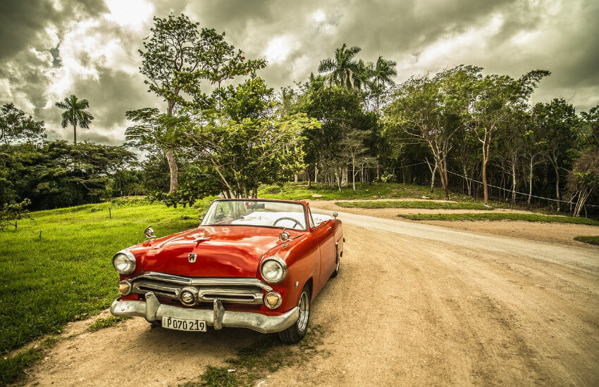 Ein roter Oldtimer steht am Straßenrand im Kuba