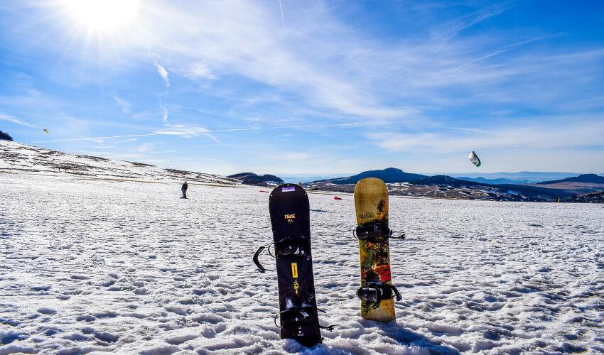 Zwei Snowboards stecken im Schnee.