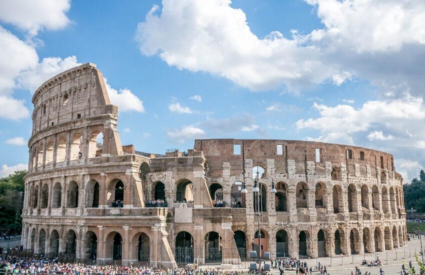 Das Kolosseum unter blauem Himmel und vielen Menschen vor dem Eingang.