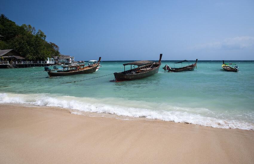 Strand, wo vier Holzboote für Touristen Ausflüge ankern.
