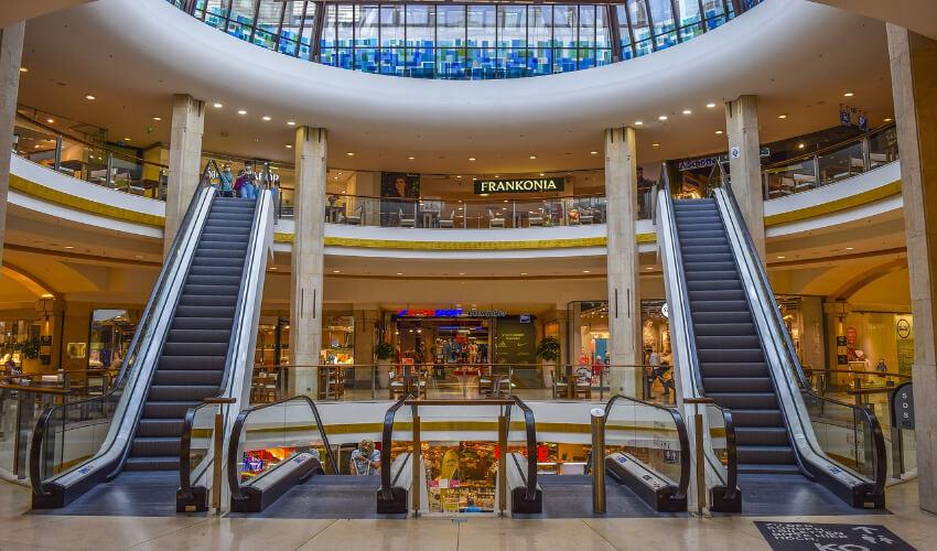 Rolltreppen in einem Einkaufszentrum. Links und rechts jeweils eine Rolltreppe, die nach oben führt und in der Mitte zwei, die nach unten laufen.