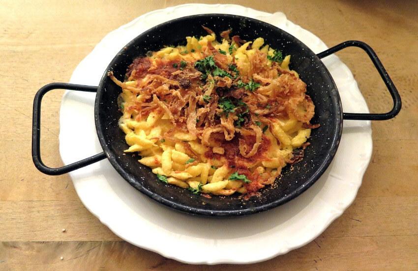 Käsespätzle mit gerösteten Zwiebeln in einer Pfanne serviert.