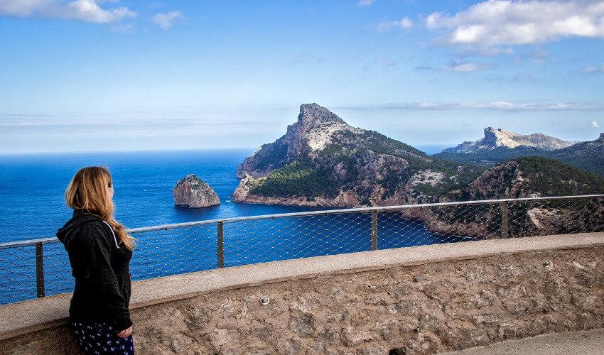 Eine Frau steht am Geländer einer Steilküste und blickt Richtung Meer.