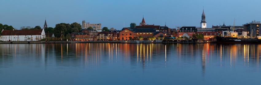 Das belebte Uferviertel von Aalborg bei Abenddämmerung.