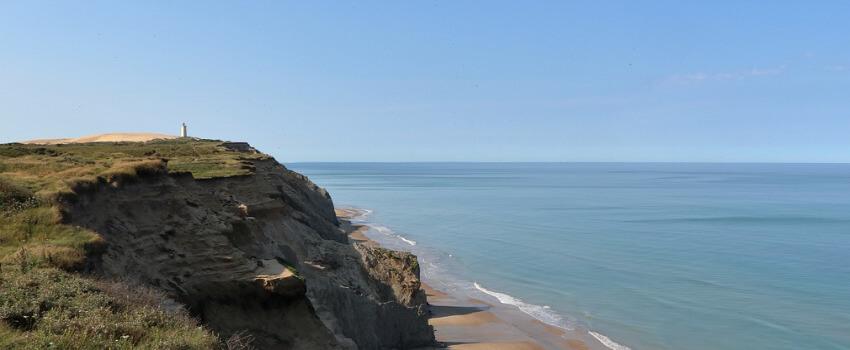 Eine hohe steile Felsklippe, darunter ein schmaler Sandstreifen.