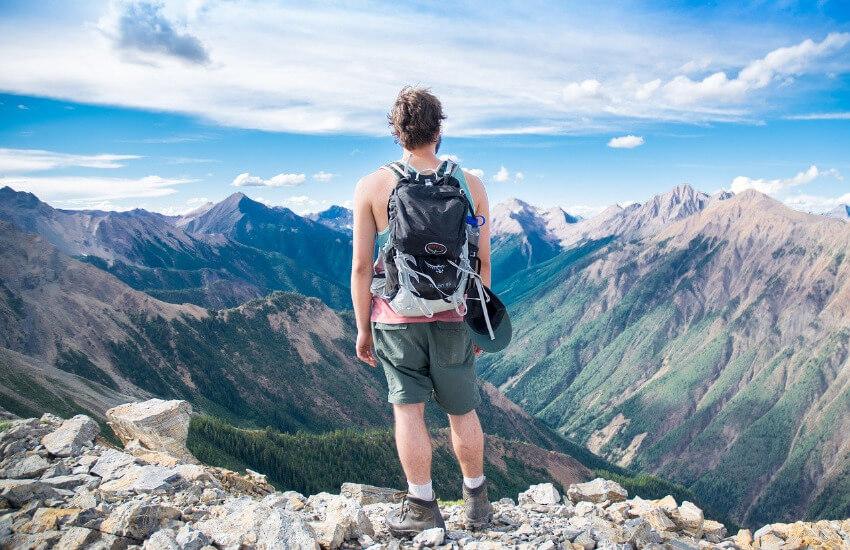 Ein Mann steht hoch oben am Berg und genießt die Aussicht.