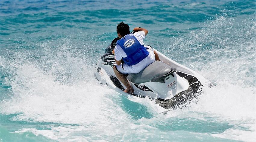 Ein Mann mit einem weißen Jetski unterwegs im blauen Meer.
