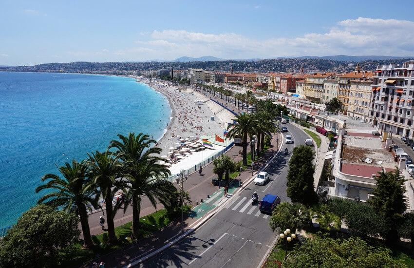 Ein lang gezogener Strand mit der Stadt Nizza direkt dahinter.