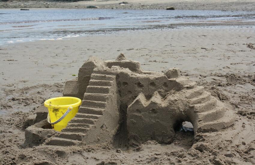 Eine kleine Sandburg und ein kleiner gelber Eimer.
