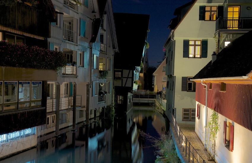 Ein kleiner Fluss fließt zischen alten Fachwerkhäusern, wobei ein Haus nach vorne kippt.