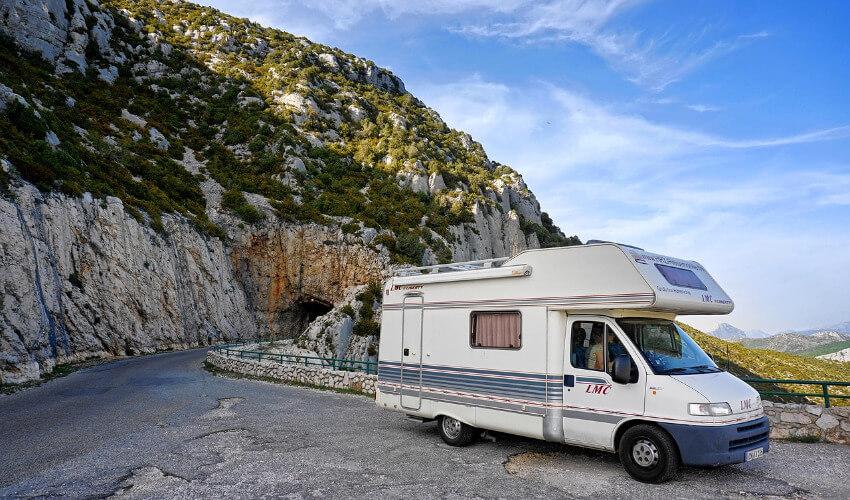 Ein Wohnmobil parkt am Rand einer kurvigen Bergstraße.