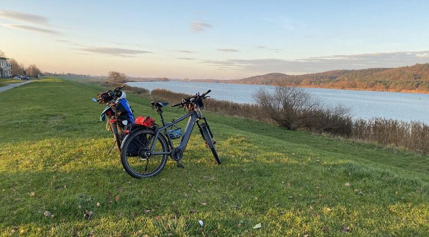 Zwei E-Bikes parken auf der Wiese und im Vordergrund die Elbe.