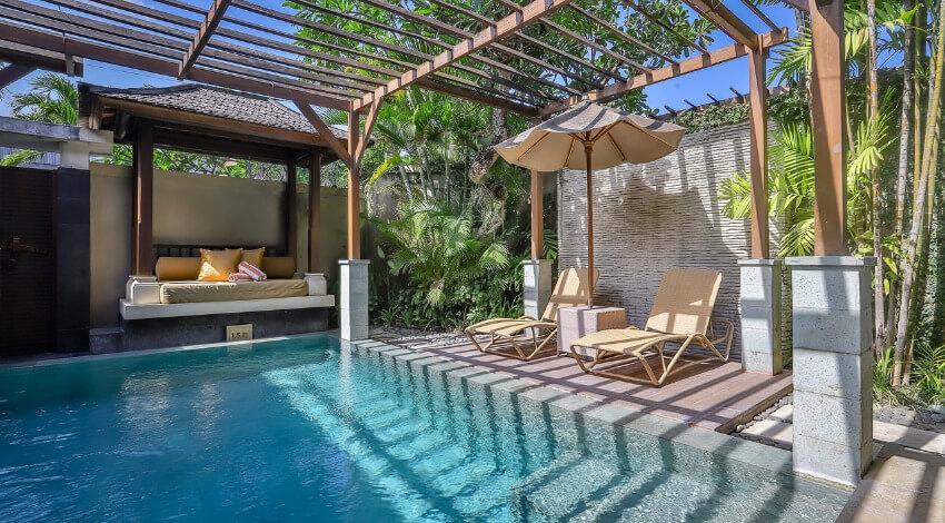 Ein Pool, wo auf einer Seite ein Schlafsofa und auf der anderen Seite 2 Liegestühle mit Sonnenschirm sich befinden.