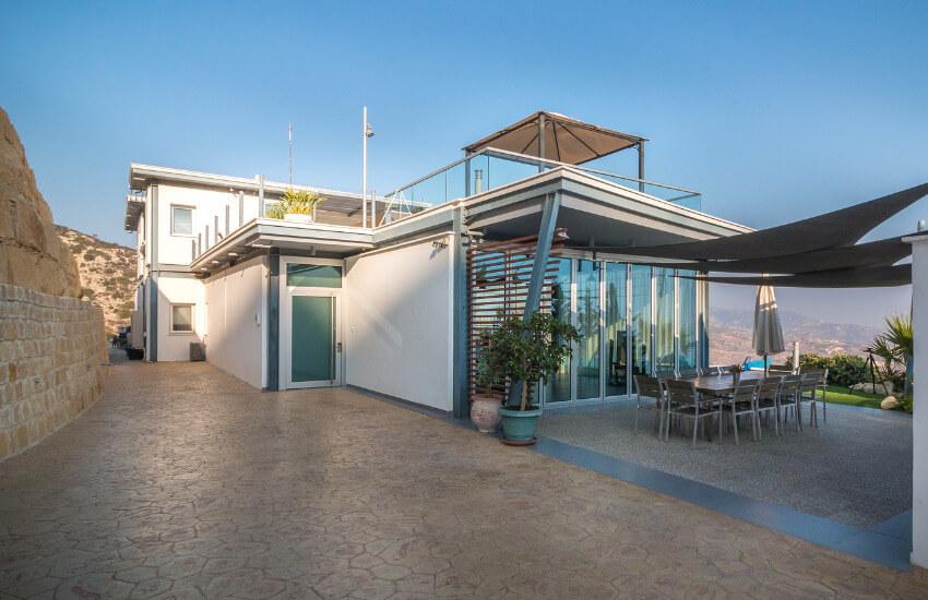 Eine kleine Villa mit einer Terrasse mit Steinpflaster und einem großen Tisch mit Stühlen.