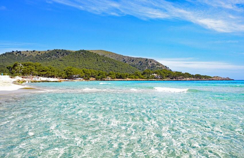 Türkises, flaches Meer mit Sandstrand und links daneben ein mit Bäumen bewachsener Hügel.