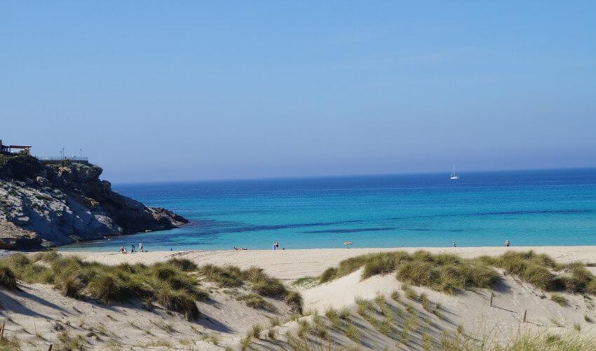 Ein weißer Sandstrand dahinter Sand mit Dünen und ein weiter Blick auf das blaue Meer.