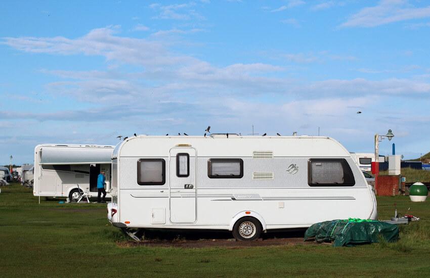 Besetzte Stellplätze für Wohnmobile auf einer Wiese auf einem Campingplatz.
