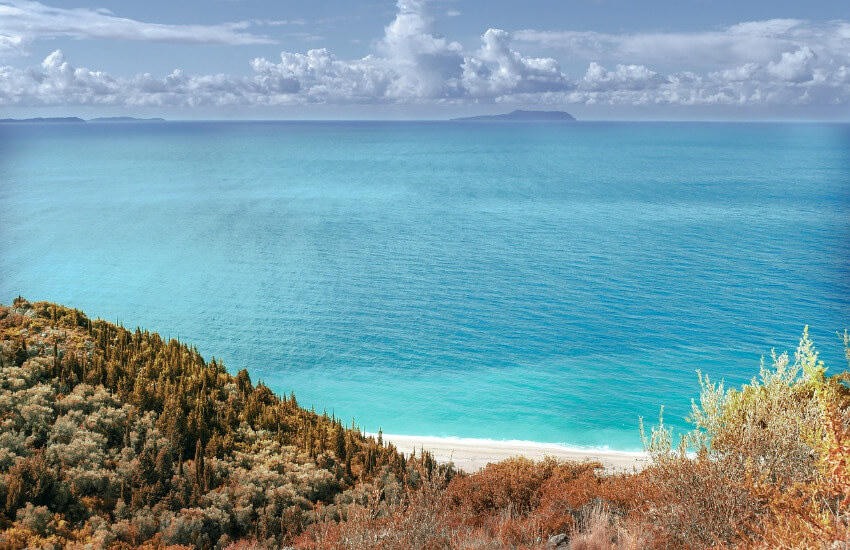 Ein toller Ausblick von einem mit Sträuchern bewachsenen Hügel auf den Strand und das türkise Meer.